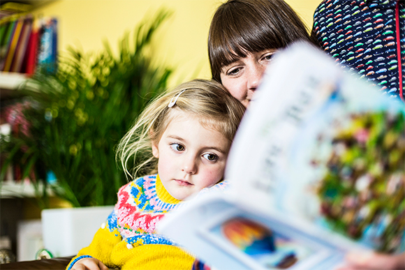 Young girl reading Life Tree book with mother